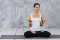 Caucasian beautiful healthy athletic sportive girl eat green apple after the training and looking at camera royalty free stock images