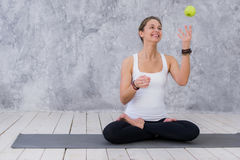 Caucasian beautiful healthy athletic sportive girl eat green apple after the training and looking at camera.  royalty free stock photography