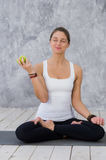 Caucasian beautiful healthy athletic sportive girl eat green apple after the training and looking at camera stock photo