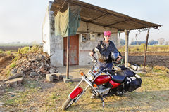 Caucasian Biker outside country shack. Fashionable, trendy, Caucasion motorcyle rider holding a helmet parked outside a rural hut earing a red bandanna Stock Photos