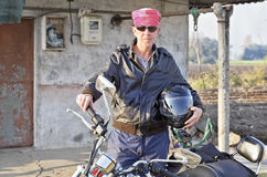 Caucasian biker outside shack hinterlands royalty free stock photos