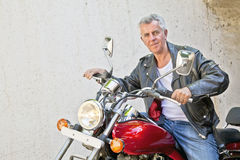 Caucasian Biker relaxed on his Motorcycle stock image