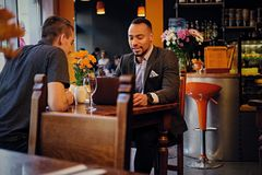 Men having a business meeting in a restaurant. Caucasian and black American men having a business meeting in a restaurant Stock Images