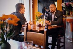 Two men talks and using a laptop in a restaurant. Caucasian and black American men talks and using a laptop in a restaurant Royalty Free Stock Images