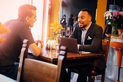 Two men talks and using a laptop in a restaurant. Caucasian and black American men talks and using a laptop in a restaurant Royalty Free Stock Photography