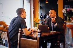 Two men talks and using a laptop in a restaurant. Caucasian and black American men talks and using a laptop in a restaurant Stock Image