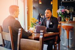 Two men talks and using a laptop in a restaurant. Caucasian and black American men talks and using a laptop in a restaurant Stock Photo