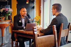 Two men talks and using a laptop in a restaurant. Caucasian and black American men talks and using a laptop in a restaurant Royalty Free Stock Image