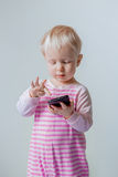 Caucasian blond baby with blue eyes making a call, playing with mobile cell phone Royalty Free Stock Photography