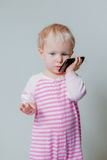 Caucasian blond baby with blue eyes talking over mobile cell phone. Cute adorable white Caucasian blond baby with blue eyes talking over mobile cell phone with Royalty Free Stock Images