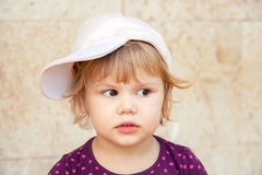 Caucasian blond baby girl in baseball cap Stock Photo