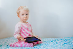 Caucasian blond baby girl sitting in bed playing with digital tablet with funny face expression. Cute adorable white Caucasian blond baby girl sitting in bed royalty free stock images