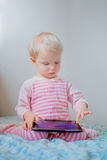 Caucasian blond baby girl sitting in bed playing with digital tablet with funny face expression. Cute adorable white Caucasian blond baby girl sitting in bed stock photography