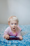 Caucasian blond baby girl sitting in bed playing with digital tablet with funny face expression. Cute adorable white Caucasian blond baby girl lying in bed royalty free stock photos