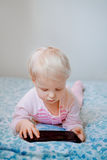Caucasian blond baby girl sitting in bed playing with digital tablet with funny face expression Royalty Free Stock Photos