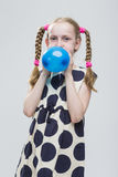 Caucasian Blond Girl With Pigtails Posing in Polka Dot Dress Against White. Stock Photo