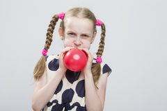 Caucasian Blond Girl With Pigtails Posing in Polka Dot Dress Against White. Royalty Free Stock Image
