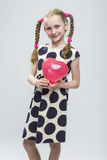 Caucasian Blond Girl With Pigtails Posing in Polka Dot Dress Against White. Royalty Free Stock Photo