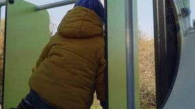 Caucasian blond stylish toddler plays on slide. On playground stock video