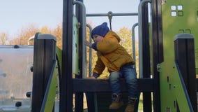 Caucasian blond stylish toddler plays on slide. On playground stock footage