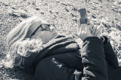 Caucasian blond teenage girl in black jacket laying in park Stock Images