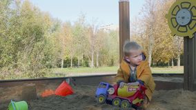 Caucasian blond toddler plays in sand pit with toy cement mixer truck. Caucasian blond toddler plays with toy cement mixer truck in sand pit on play ground stock video footage