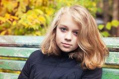 Caucasian blond tonårs- flicka i svart omslag royaltyfri bild