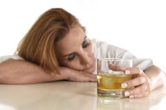 Caucasian blond wasted and depressed alcoholic woman drinking scotch whiskey glass messy drunk Royalty Free Stock Images