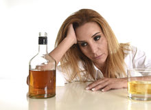 Caucasian blond wasted and depressed alcoholic woman drinking scotch whiskey glass messy drunk Stock Images