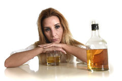 Caucasian blond wasted and depressed alcoholic woman drinking scotch whiskey glass messy drunk. Caucasian blond wasted and depressed alcoholic woman drinking Royalty Free Stock Image