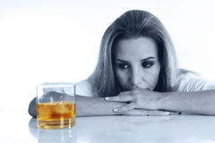 Caucasian blond wasted and depressed alcoholic woman drinking scotch whiskey glass messy drunk Royalty Free Stock Photography