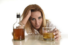 Caucasian blond wasted and depressed alcoholic woman drinking scotch whiskey glass messy drunk. Caucasian blond wasted and depressed alcoholic woman drinking Royalty Free Stock Photo