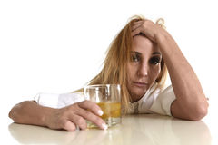 Caucasian blond wasted and depressed alcoholic woman drinking scotch whiskey glass messy drunk Royalty Free Stock Photos