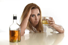 Caucasian blond wasted and depressed alcoholic woman drinking scotch whiskey glass messy drunk. Caucasian blond wasted and depressed alcoholic woman drinking Stock Images