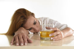 Caucasian blond wasted and depressed alcoholic woman drinking scotch whiskey glass messy drunk Stock Photos