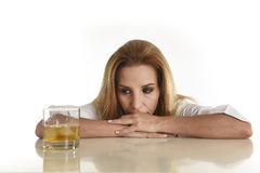 Caucasian blond wasted and depressed alcoholic woman drinking scotch whiskey glass messy drunk. Caucasian blond wasted and depressed alcoholic woman drinking Stock Image
