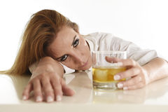 Caucasian blond wasted and depressed alcoholic woman drinking scotch whiskey glass messy drunk Royalty Free Stock Image