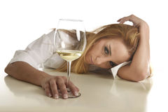 Caucasian blond wasted and depressed alcoholic woman drinking wh Royalty Free Stock Images
