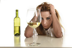 Caucasian blond wasted and depressed alcoholic woman drinking white wine glass drunk hangover Royalty Free Stock Image