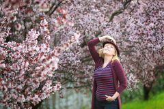 Caucasian blond woman with long hair in purple fedora hat near blossoming tree. One hand up stock photos
