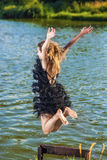 Caucasian Blond Woman in Dress Jumping Near Water Shore. Royalty Free Stock Photo
