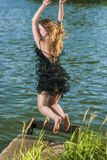 Caucasian Blond Woman in Dress Jumping Near Water Shore Royalty Free Stock Photography