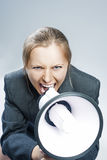 Caucasian Blond Woman Shouting Using Megaphone. Against Grey Bac Stock Image