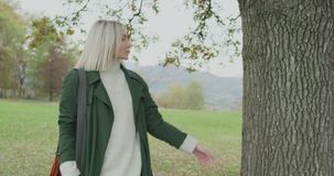 Caucasian blond woman slomo walking toward fall woods touching tree. Following in front gimbal. Storytelling real young stock video footage