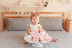 Caucasian blonde baby girl in white dress celebrating her first birthday. Portrait of cute adorable Caucasian blonde baby girl in white dress celebrating her royalty free stock photos