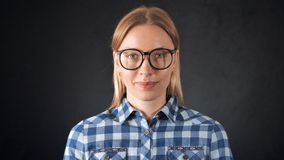 Portrait adult candid woman with blond hair. Caucasian blonde female posing in studio on black background friendly smiling. smart girl wearing eyeglasses casual stock footage