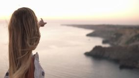 Caucasian blonde girl admiring evening scene of the sunset sky above the sea.S tanding on the cliff and pointing on. Horizon. Wind blowing her hair stock footage
