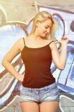 Caucasian blonde girl in denim shorts and black tank top po royalty free stock image