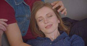 Caucasian blonde girl lying on his boyfriend`s knees and they talking with each other at cozy home. Caucasian blonde girl lying on his boyfriend`s knees and stock footage