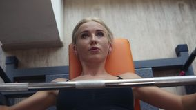 Caucasian blonde woman in black sport bra training with bar on bench in the gym with panoramic windows. Concentrated on stock video footage